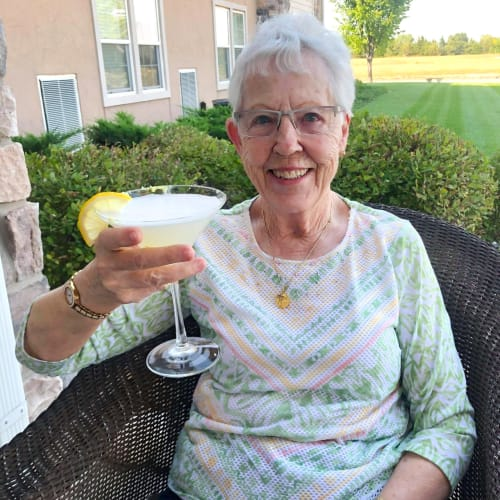 Resident relaxing outside with a mixed drink at The Oxford Grand Assisted Living & Memory Care in Wichita, Kansas