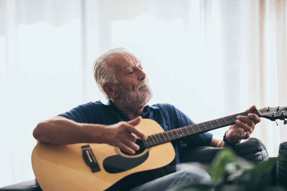 Resident sitting and playing an acoustic guitar at Canoe Brook Assisted Living in Duncan, Oklahoma