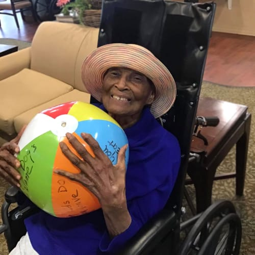 Resident holding a beach ball at Oxford Glen Memory Care at Grand Prairie in Grand Prairie, Texas