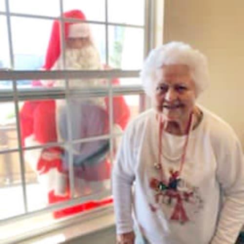 A resident visiting with santa through a window at Alderbrook Village in Arkansas City, Kansas
