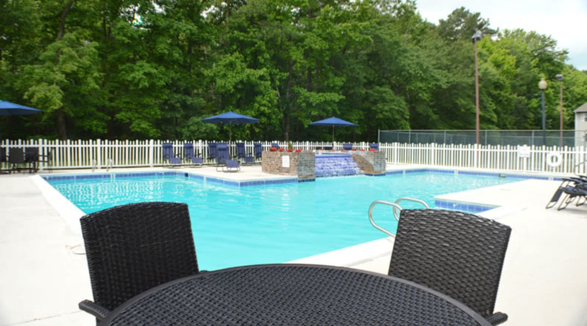 Patio seating next to the swimming pool and water feature at Laurel Pines Apartments in Richmond, Virginia