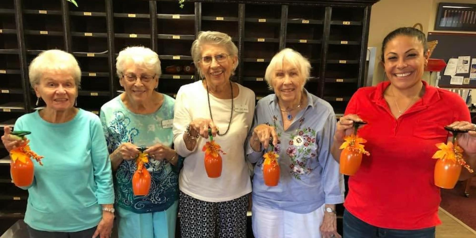 Residents and staff holding decorated cups at Paloma Landing Retirement Community in Albuquerque, New Mexico