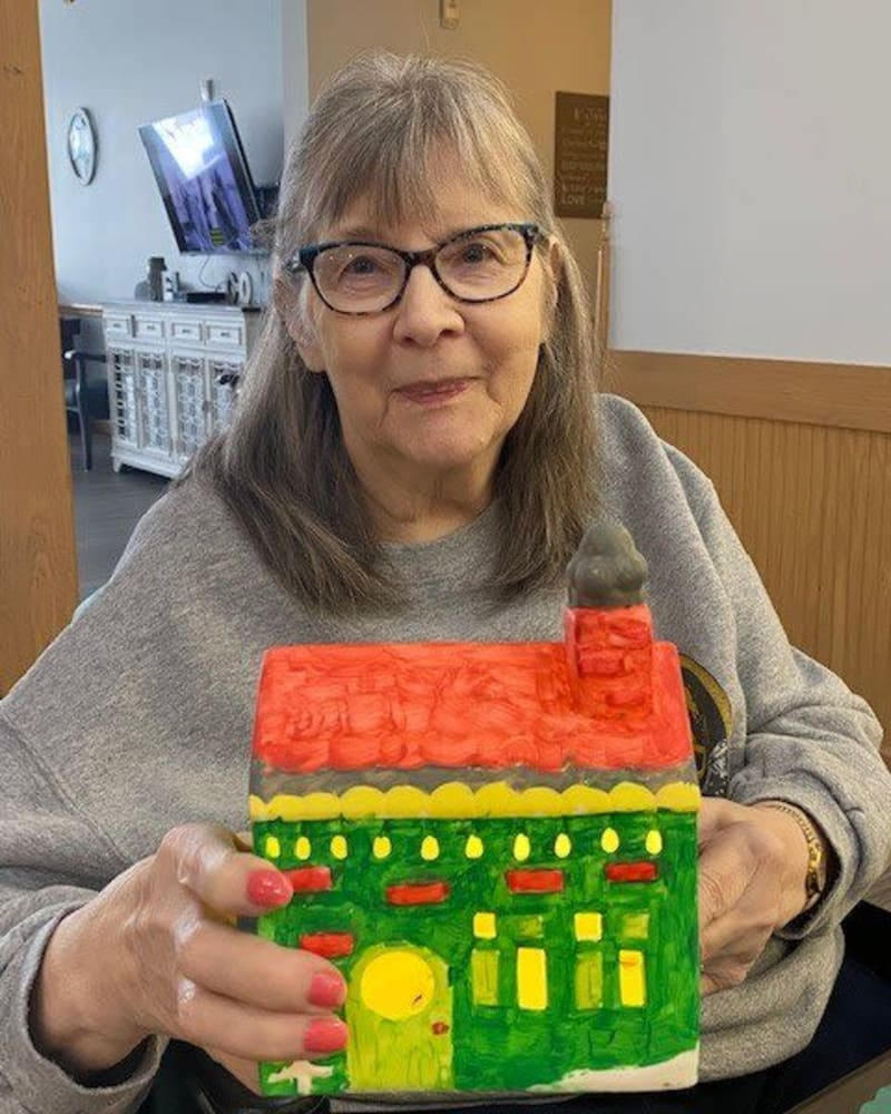 Resident holding a gingerbread house at Apple Creek Place in Appleton, Wisconsin