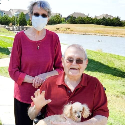 Resident couple out for a walk with their dog at The Oxford Grand Assisted Living & Memory Care in Wichita, Kansas