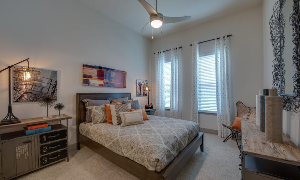 Decorated bedroom with ceiling fan and carpet at Bellrock Upper North in Haltom City, Texas