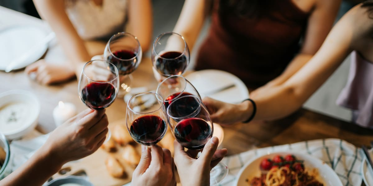 Residents enjoying a glass of wine at dinner near Marquis at Crown Ridge in San Antonio, Texas