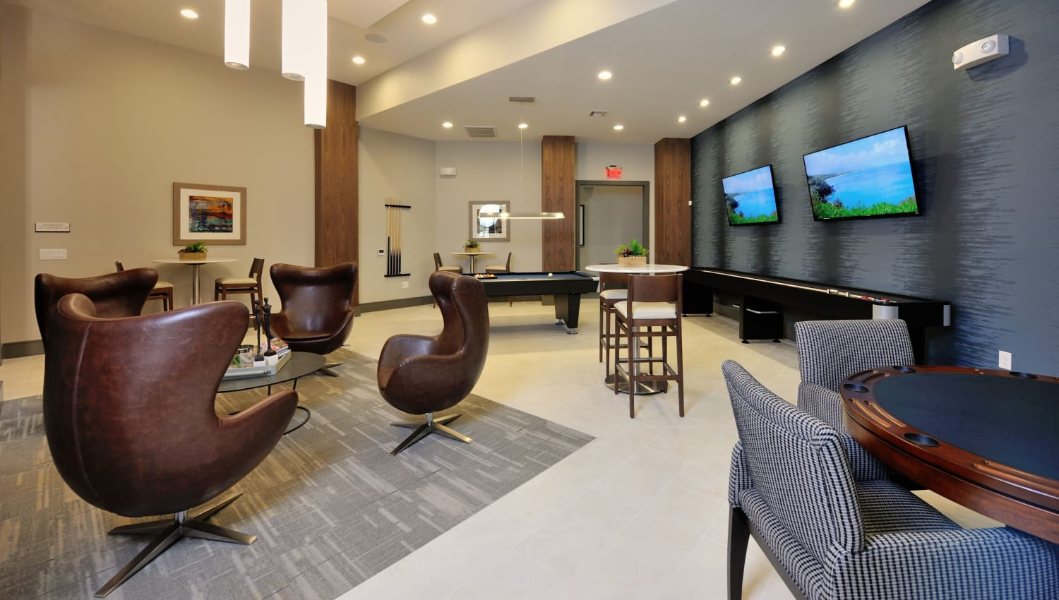 Resident lounge with TVs at Olympus Falcon Landing in Katy, Texas