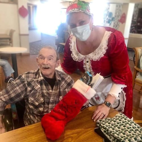 A resident receiving a stocking from a caretaker at Ashbrook Village in Duncan, Oklahoma