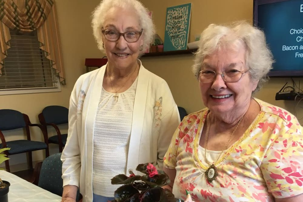 Two female residents potting plants indoors at Stonegate Health Campus in Lapeer, Michigan