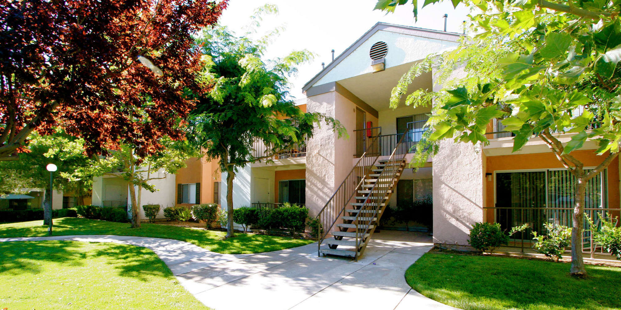 Mature trees and professionally maintained landscaping outside resident buildings at Mountain Vista in Victorville, California