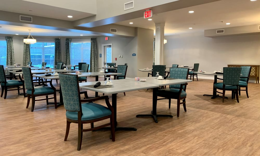 A large dining room with set tables at Keystone Place at Wooster Heights in Danbury, Connecticut