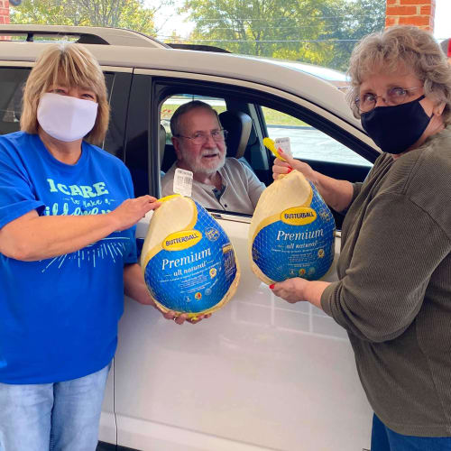 Masked caretakers delivering food to residents vehicles at Canoe Brook Assisted Living in Ardmore, Oklahoma