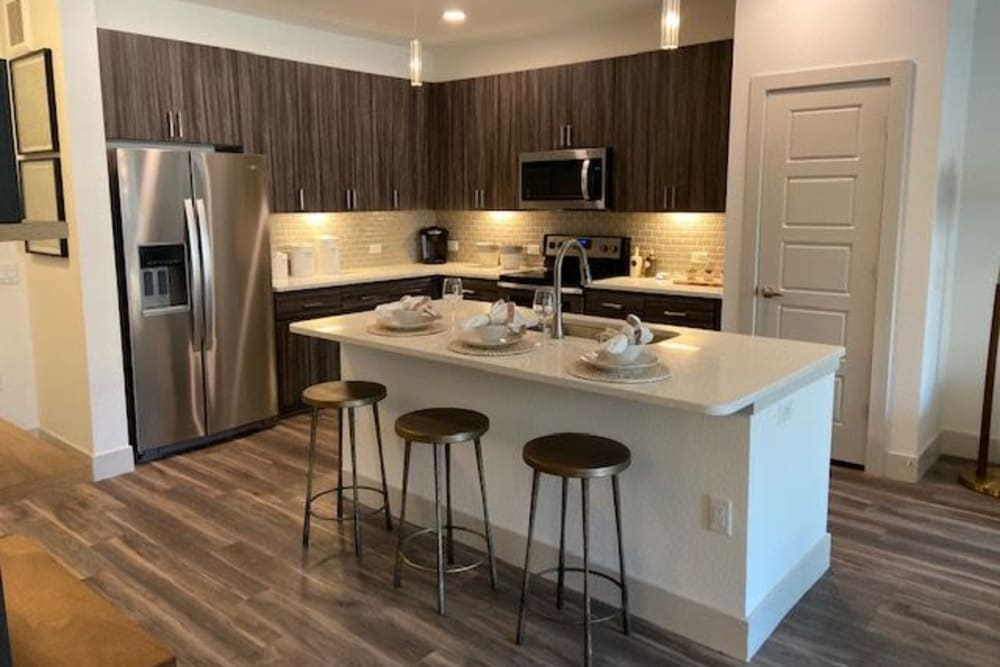 Modern Kitchen With Stainless Steel Appliaces At The District at Chandler In Chandler, Arizona features breakfast bar seating and stainless steel appliances