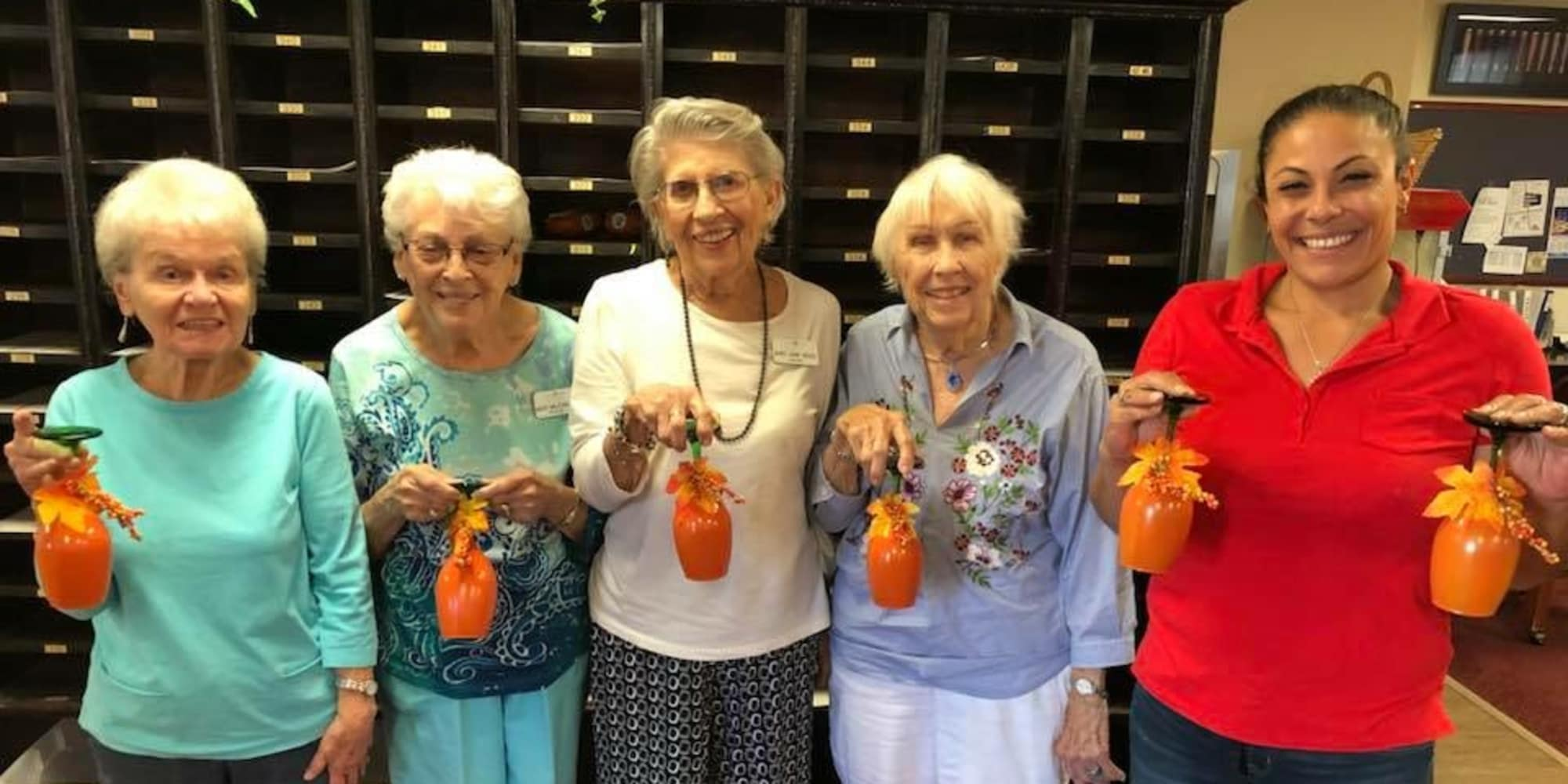 Residents holding decorated cups at Sanford Estates Gracious Retirement Living in Roswell, Georgia