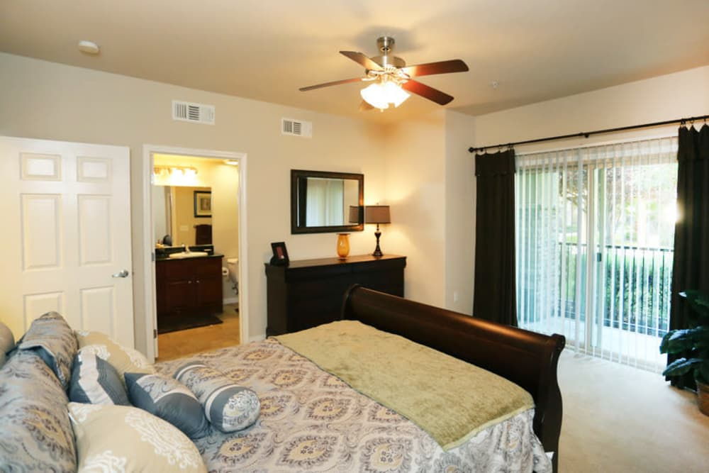 Model bedroom with ceiling fan at Wolf Ranch Condominium Rentals in Sacramento, California