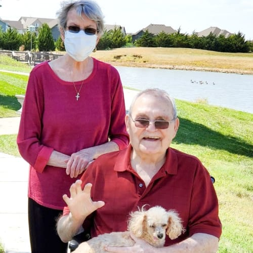 Resident couple outside by a lake with their dog at The Oxford Grand Assisted Living & Memory Care in Wichita, Kansas