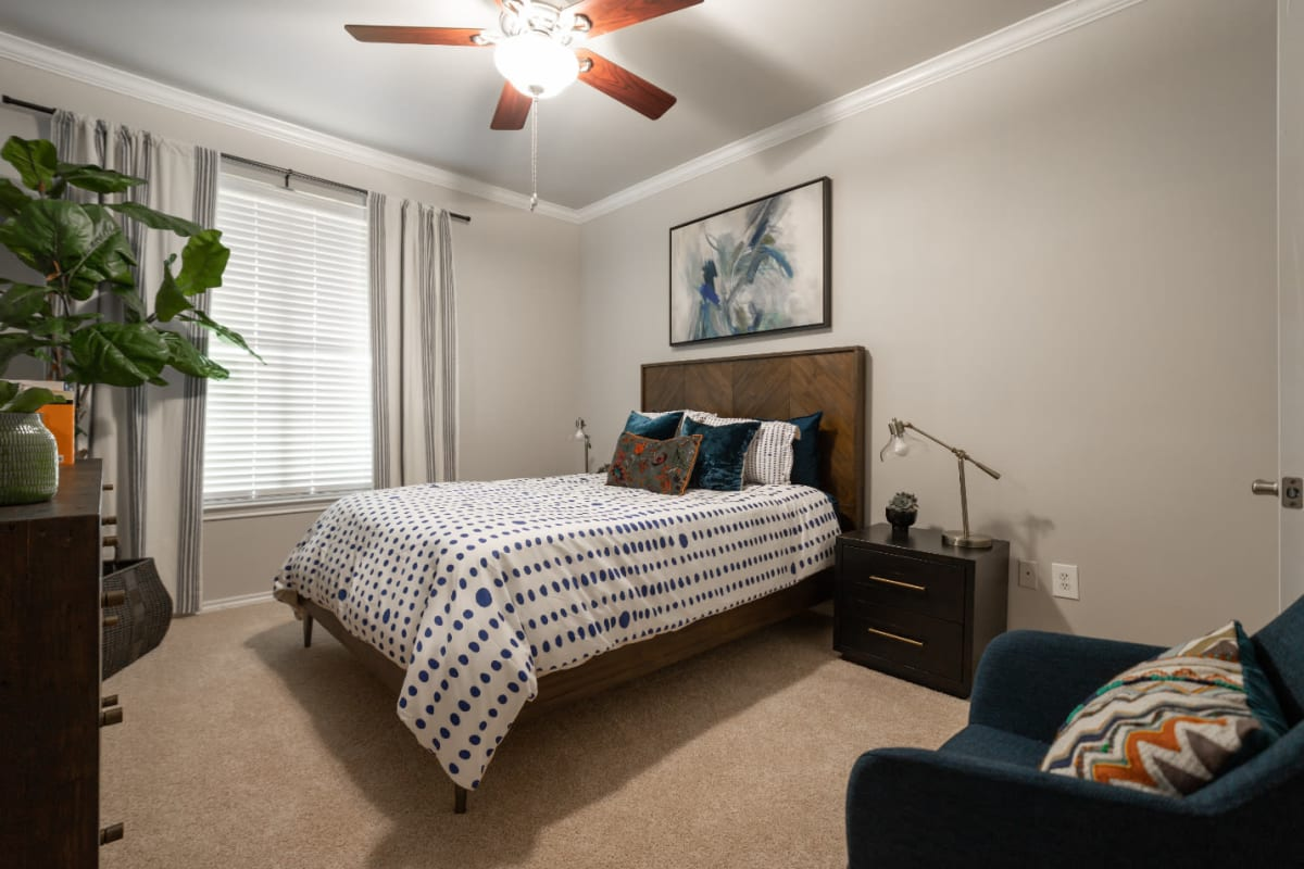Carpeted bedroom with ceiling fan at Marquis at Bellaire Ranch in Fort Worth, Texas