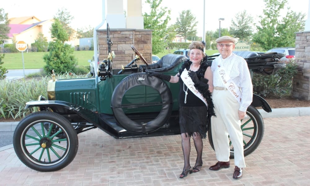 Residents posing for a picture in front of a vintage automobile at Ashwood Meadows Gracious Retirement Living in Johns Creek, Georgia