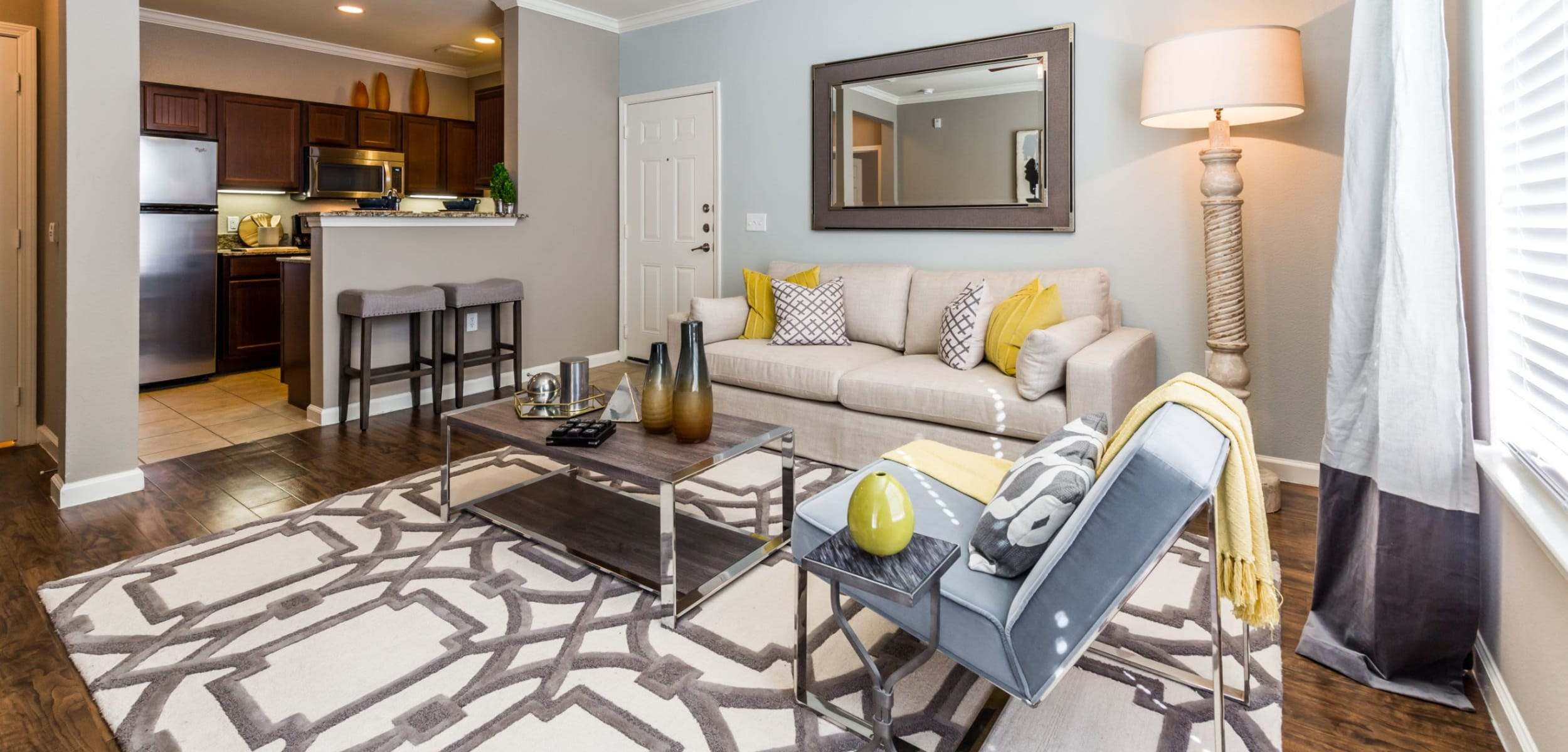 Open and bright living area with wood floors and a large rug at Marquis at Crown Ridge in San Antonio, Texas