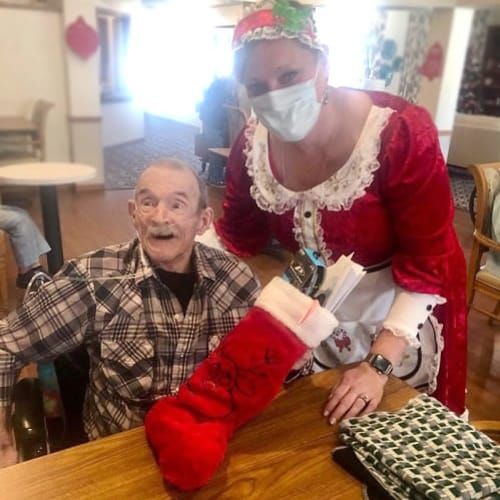 excited resident getting a stocking from a caretaker at Ashbrook Village in Duncan, Oklahoma
