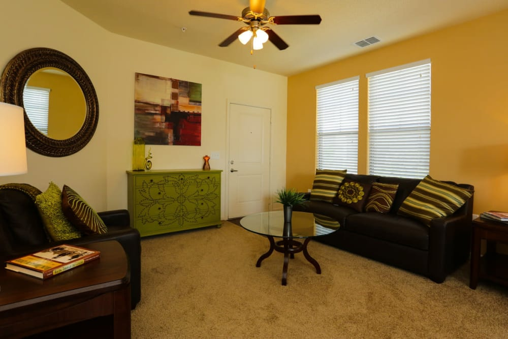 Ceiling fan and plush carpeting in a model home's living area at The Hawthorne in Jacksonville, Florida