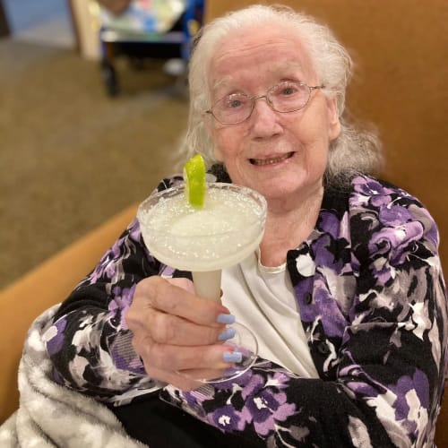 Resident holding a margarita at Oxford Glen Memory Care at Carrollton in Carrollton, Texas