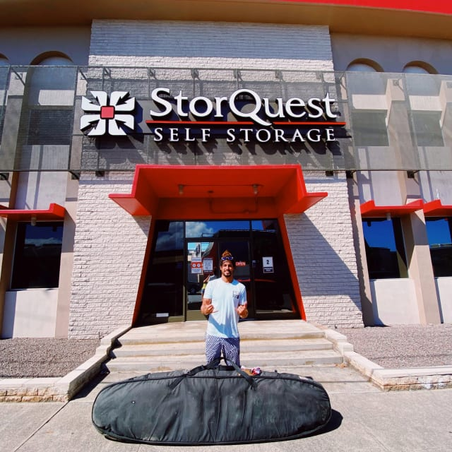 Man standing outside storquest location with surf gear