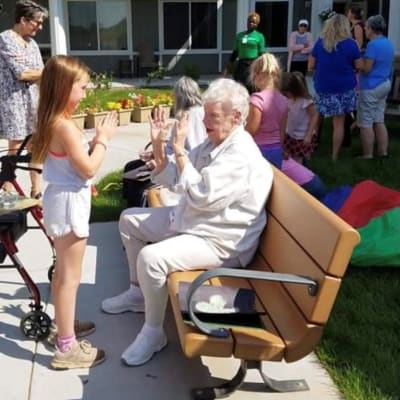 A young girl plays patty-cake with a resident near Arbor Glen Senior Living in Lake Elmo, Minnesota