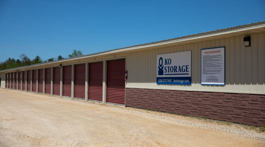 Exterior view of a row of storage units with brown doors at KO Storage of Tomah - McCoy in Tomah, Wisconsin
