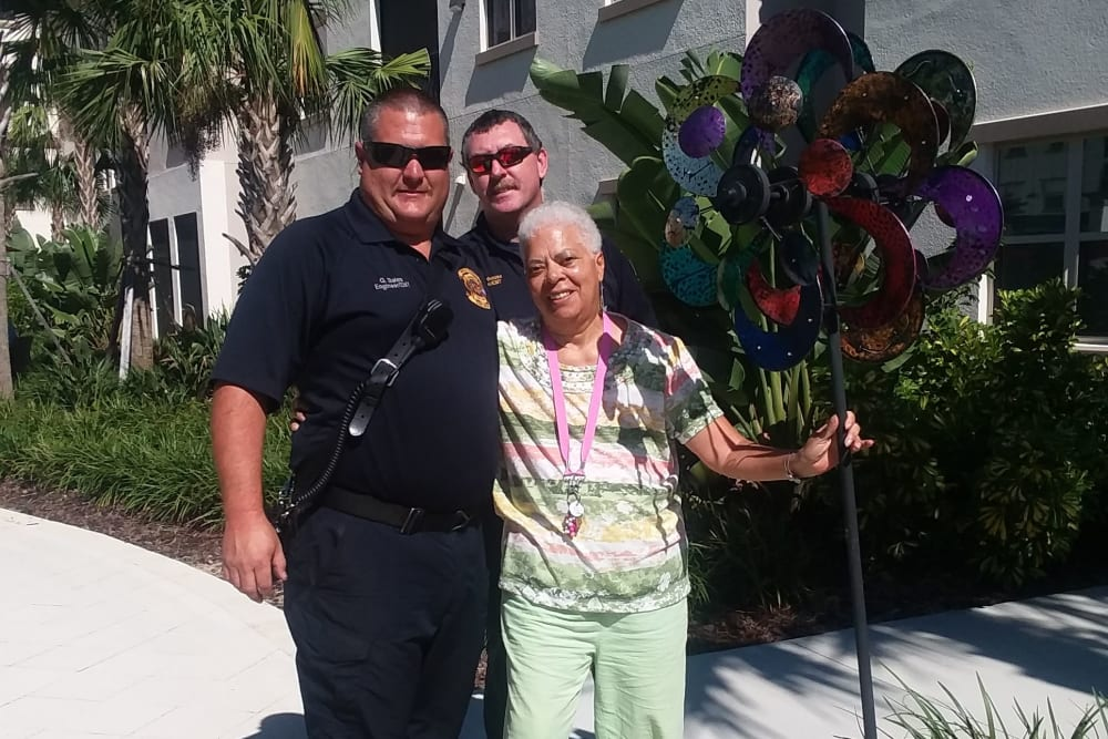 Resident poses for a photo with staff at Merrill Gardens at ChampionsGate in ChampionsGate, Florida.