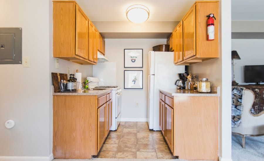 Wood cabinetry and granite countertops in model home's kitchen at Westgate Apartments & Townhomes in Manassas, Virginia
