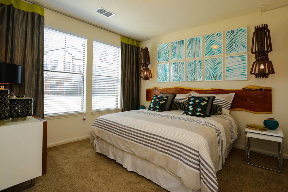 Model home's master bedroom with a ceiling fan at The Hawthorne in Jacksonville, Florida