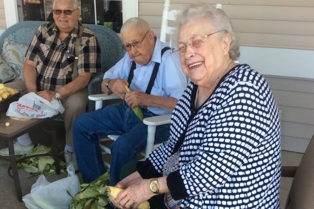 Residents shuck corn on the porch at Clover Ridge Place in Maquoketa, Iowa.