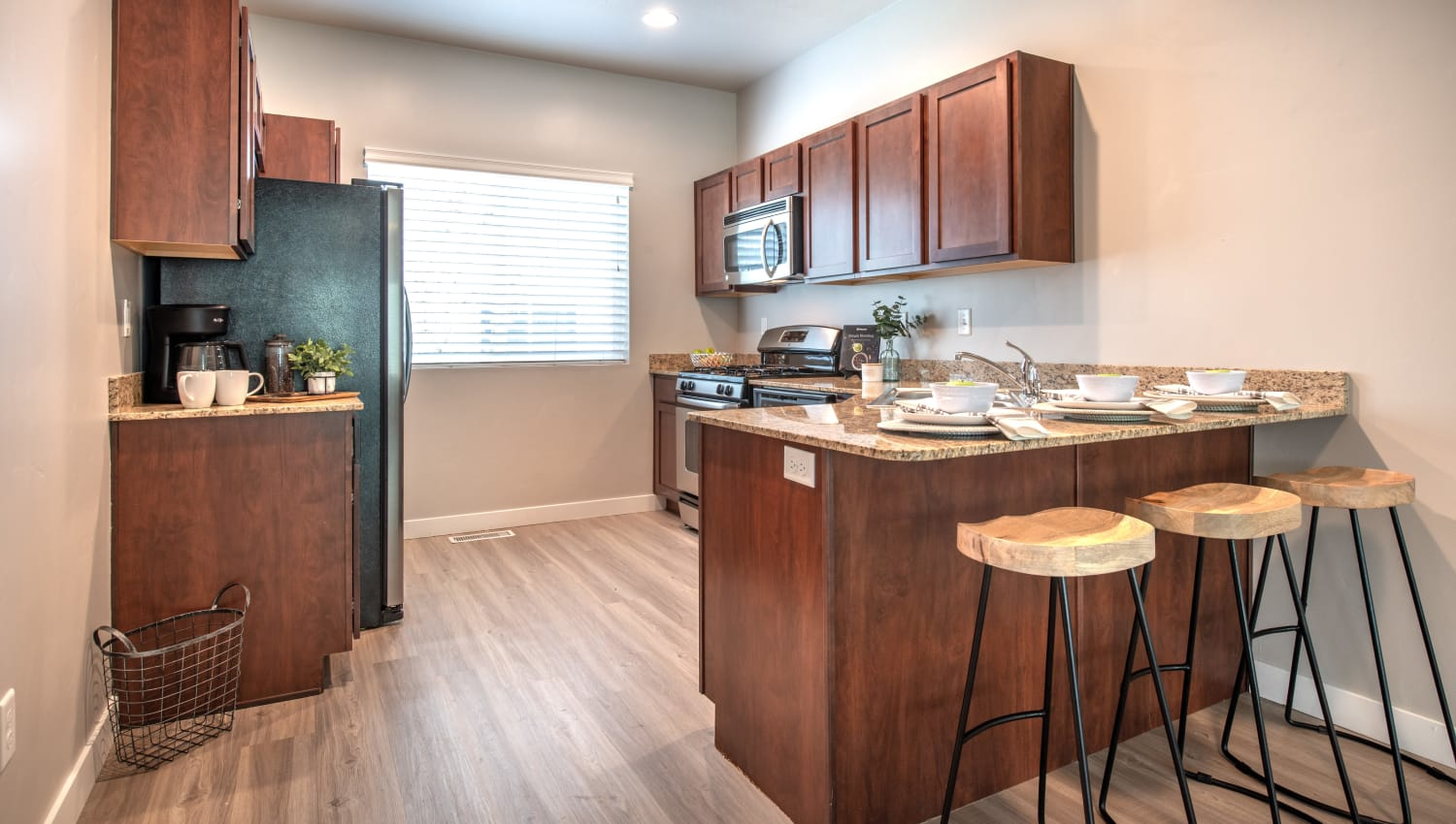 Kitchen at Olympus at the District in South Jordan, Utah features breakfast bar seating area