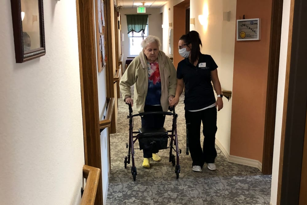 Staff provides assistance to resident with walker at Landings of Sauk Rapids in Sauk Rapids, Minnesota