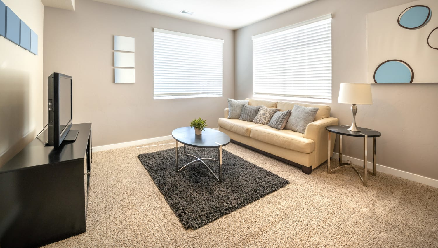 Spacious living room  at Olympus at the District in South Jordan, Utah features ample natural light from large windows