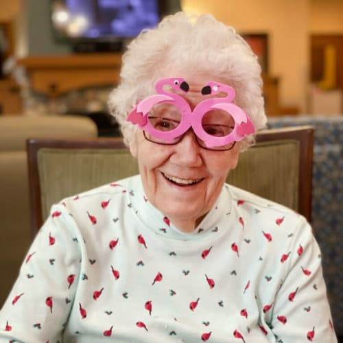 A resident wearing bright pink flamingo style glasses at Glen Carr House Memory Care in Derby, Kansas