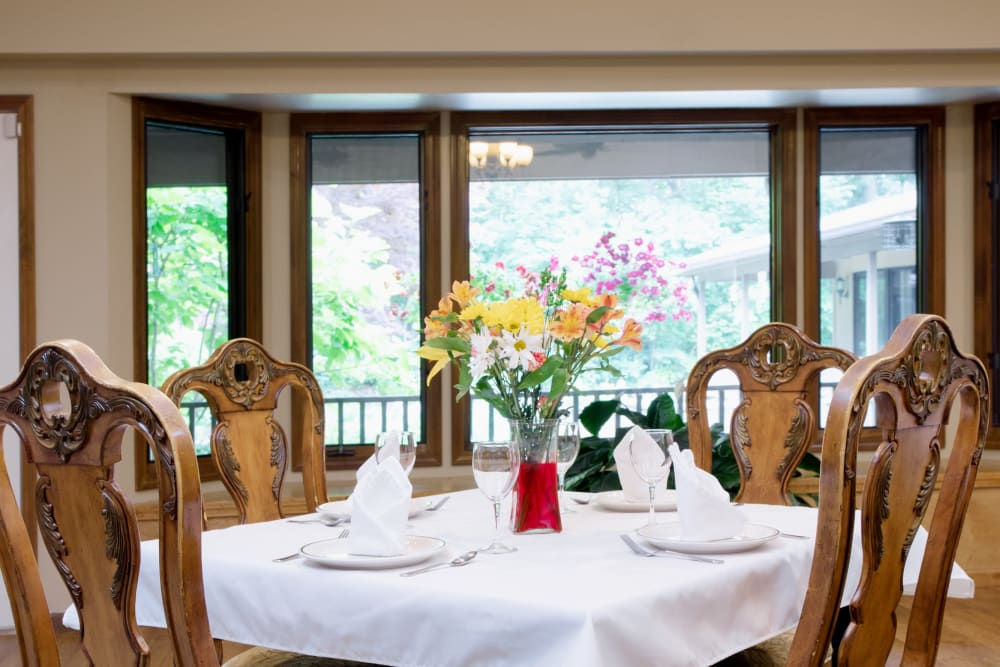 Square dining table with a white tablecloth and a floral centerpiece at Lakeshore Woods in Fort Gratiot, Michigan