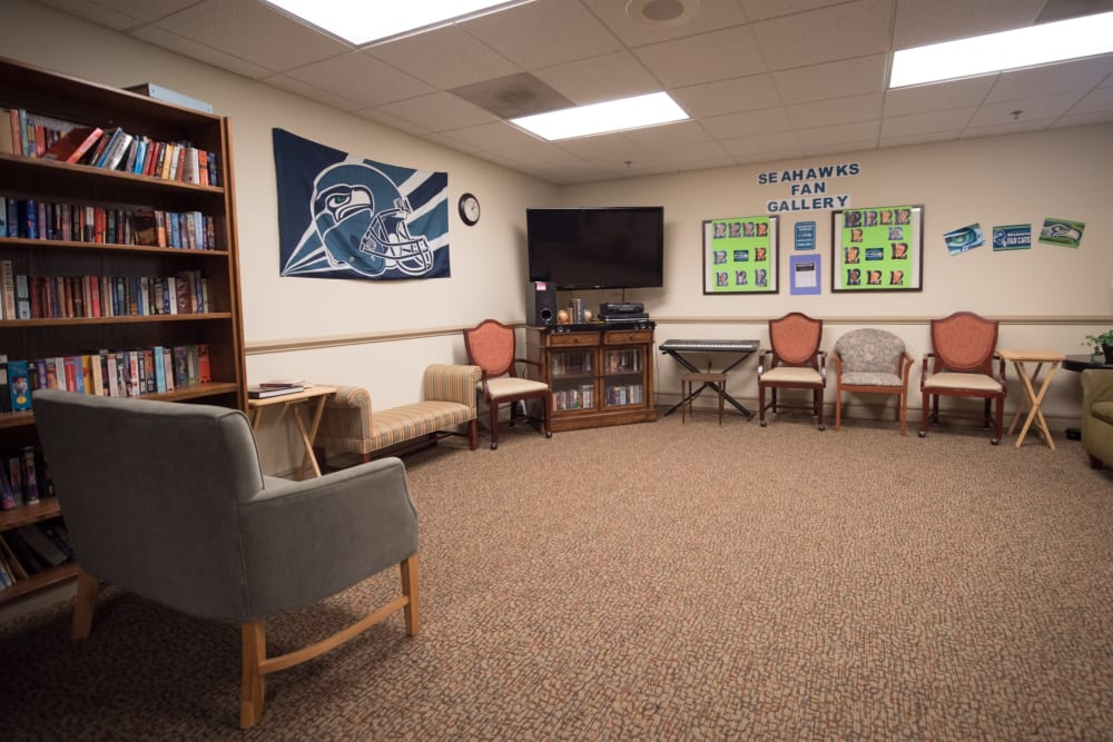 Community room with chairs and TV at Kenmore Senior Living in Kenmore, Washington