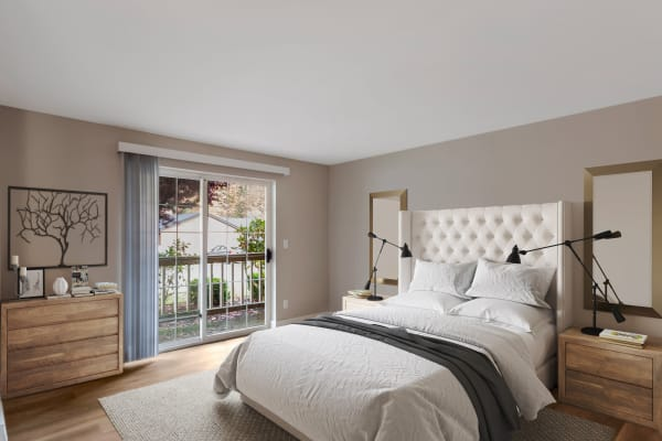 Beautifully decorated model bedroom with sliding door access to a private patio at Chandlers Bay Apartments in Kent, Washington