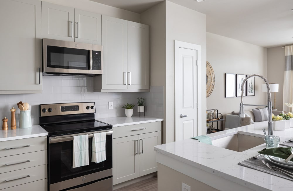 Modern kitchen with quartz countertops and stainless-steel appliances in a model apartment at a luxury community by Electra America in Lake Park, Florida