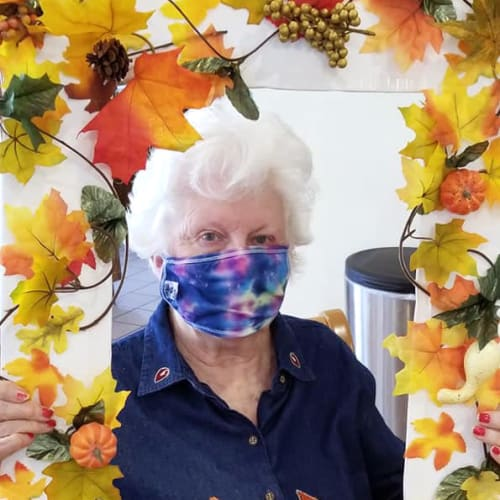 A masked resident holding up a floral picture frame at Ashbrook Village in Duncan, Oklahoma
