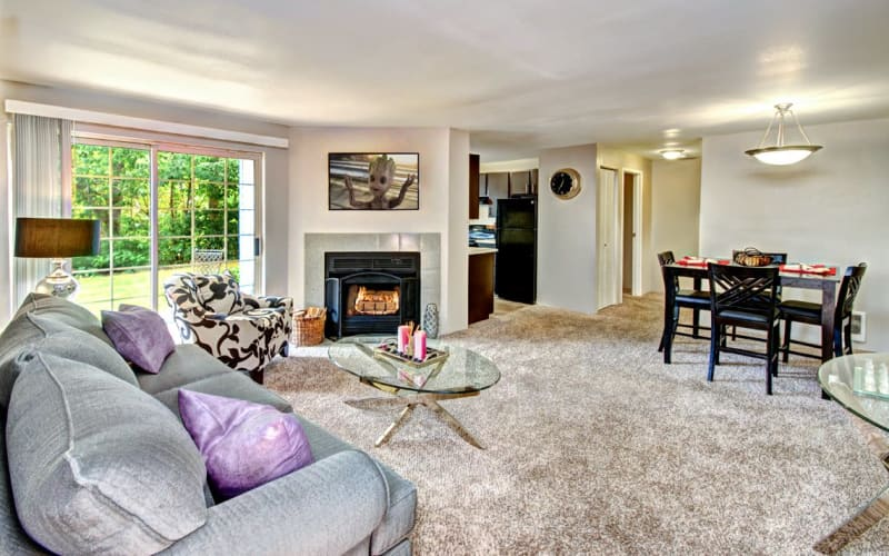 Spacious living room with plush carpeting and a fireplace at Wellington Apartment Homes in Silverdale, Washington