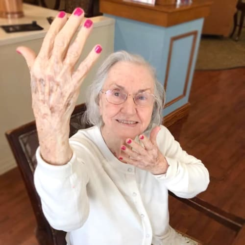 Resident showing off her brightly painted nails at Oxford Glen Memory Care at Grand Prairie in Grand Prairie, Texas