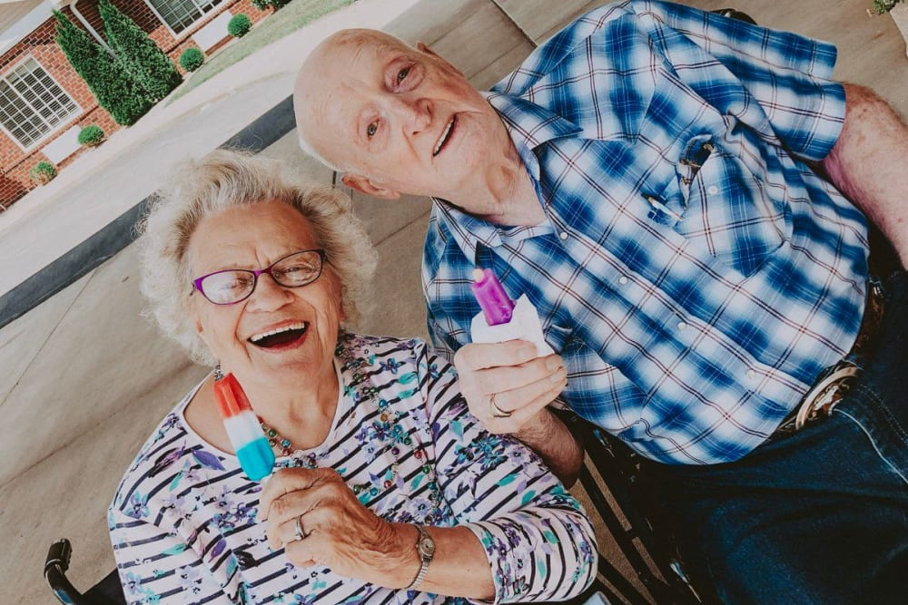 Male and Female resident eating popsicles outside on a beautiful day at Village Green Health Campus in Greenville, Ohio