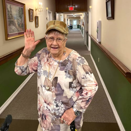 A resident standing in a hallway waving at the camera at Canoe Brook Assisted Living in Duncan, Oklahoma
