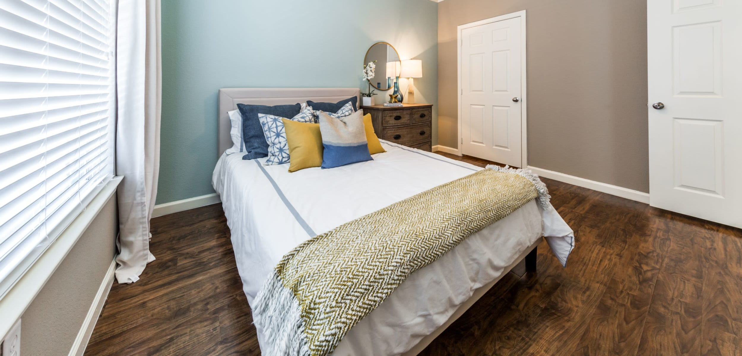 Bedroom with wood floors and a large window at Marquis at Crown Ridge in San Antonio, Texas