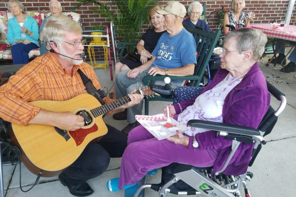 A resident listening to a musical guest at Ashford Place Health Campus in Shelbyville, Indiana