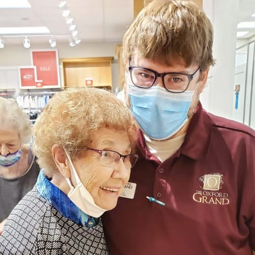 Resident hugging a masked caretaker at The Oxford Grand Assisted Living & Memory Care in Wichita, Kansas