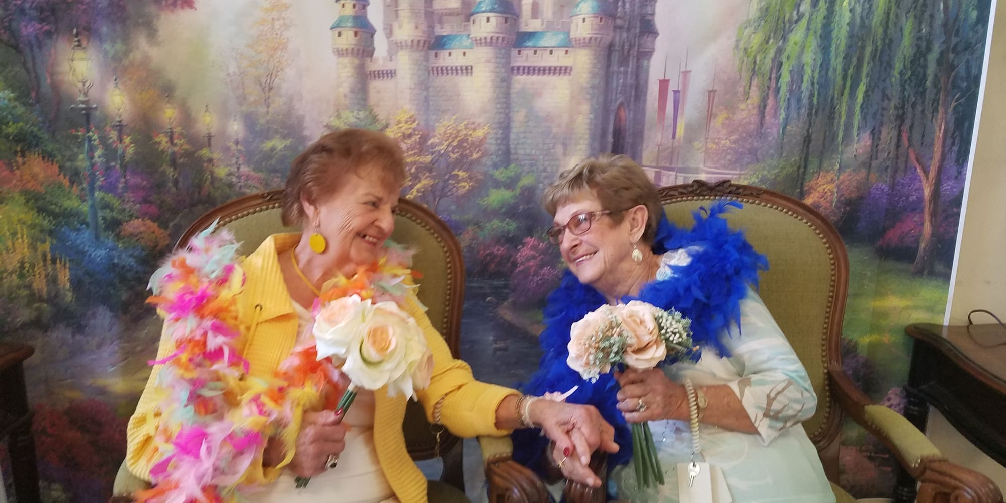 Two happy residents holding hands in front of a castle backdrop at Winterberry Heights Assisted Living in Bangor, Maine